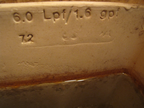 6 Liters aka 1.6 gallons per flush stamped on the inside of toilet tank