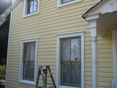 yellow clapboard wood ladder