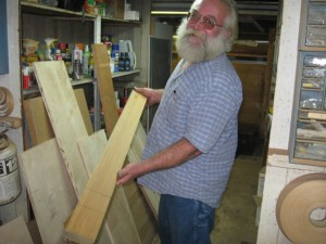 Bill, the House Mechanic, shows off wood salvaged from the bottom of a pickle barrel