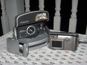 picture at night of various cameras on a wicker table polaroid