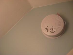 smokey smoke detector hung on a light blue wall