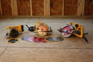Circular Saws and Saw Blades Sitting on an Unfinished Floor