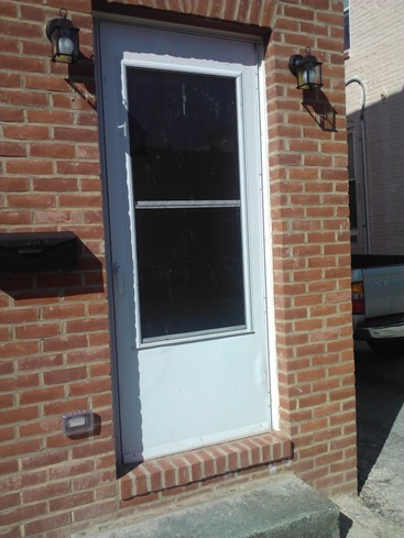 black door self storing white storm door with wear