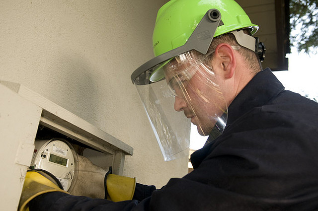 utility employee changing an energy meter via Flickr