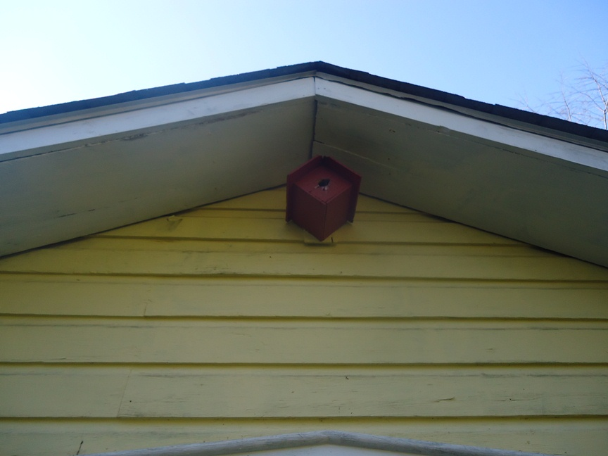 a red four square birdhouse on a shed for inspiration