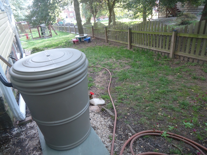 rain barrel on hill where runoff occurred because of no gutter or downspout