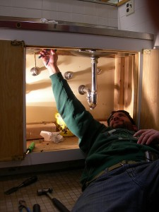 man working on under sink plumbing image via Gillece Services