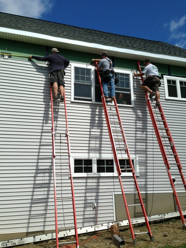 3 man on ladders with toolbelts hanging siding